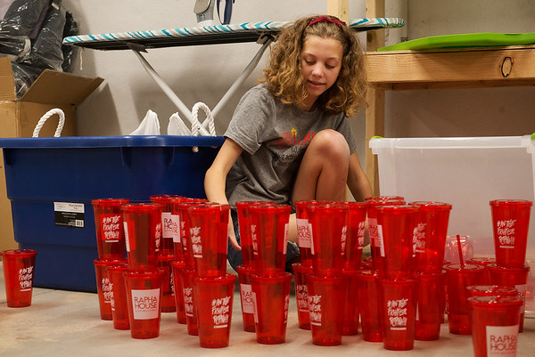 Riley Hawn, 14, sorts merchandise at Rapha House while volunteering with the Youth Volunteer Corps on Tuesday.<br /> Globe | Roger Nomer
