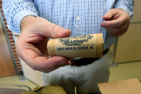 Joplin MUseum Complex curator Chris Wiseman holds a small, coarse roll of toilet paper included in K rations in preparation for a D-Day exhibit on Wednesday at the museum in honor of the 75th Anniversary of the invasion of Normandy.<br /> Globe | Laurie SIsk