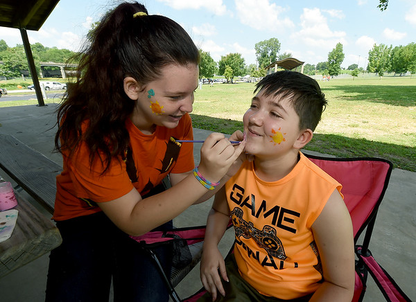 """Evelena Ruddick, 14 and Michael Potts, 13, both of Kids for Peace, paint positive messages on their faces during """"Joplin Wear Orange"""" on Saturday at Landreth Park. The event, organized by Moms Demand Action, advocated stemming gun violence while still respecting the Second Amendment.<br /> Globe 