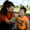 "Evelena Ruddick, 14 and Michael Potts, 13, both of Kids for Peace, paint positive messages on their faces during ""Joplin Wear Orange"" on Saturday at Landreth Park. The event, organized by Moms Demand Action, advocated stemming gun violence while still respecting the Second Amendment.<br /> Globe 