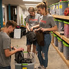 (from left) Luke Goodhope, 17, Claire Owen, 17, and Grace Loy, 15, look over merchandise at Rapha House as they volunteer with the Youth Volunteer Corps on Tuesday.<br /> Globe | Roger Nomer