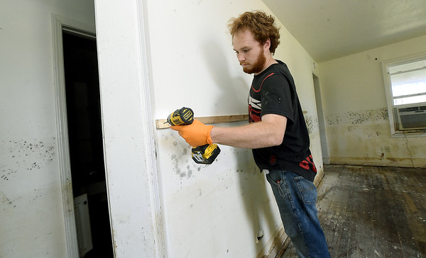 Robby DeYoung, of Moore Construction, marks a mold line for removal of drywall inside a house on the 1100 block of Central Ave. on Wednesday.<br /> Globe | Laurie SIsk
