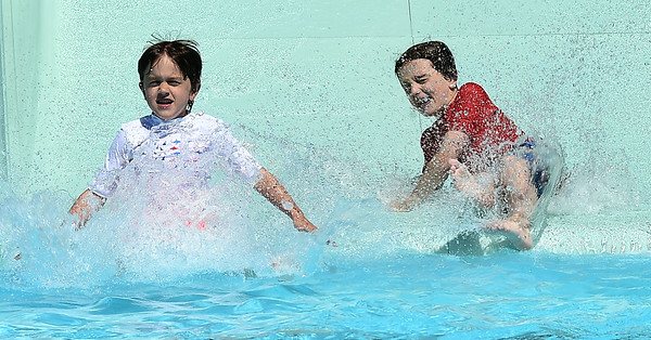 From the left: Brothers Finnegan Pratt, 6 and Benjy Pratt, 10, enjoy a trip down a slide at Schifferdecker Pool on Thursday.<br /> Globe | Laurie Sisk