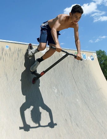 Isiah Burkett, 14, perfects his scooter skills on Thursday at the Ewert Park Skate Park. Since installation, the ramps have been a popular gathering place for skateboardists, cyclists and scooter enthusiasts.<br /> Globe | Laurie Sisk