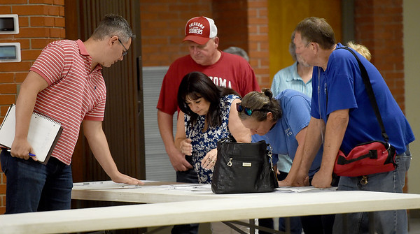 Ed Mekeel, EPA Region 6 Community Involvement Coordinator, checks residence in to an informational meeting at the Miami Civic Center on Thursday night involving the clean up of asbestos at the BF Goodrich plant in Miami. <br /> Globe | Laurie Sisk