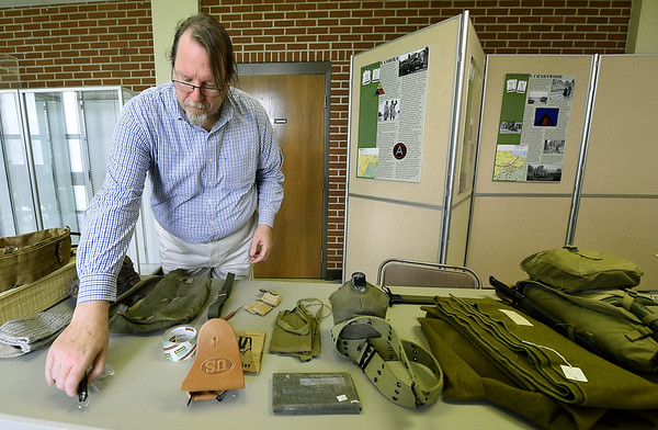 Joplin MUseum Complex curator Chris Wiseman arranges World War II relics in preparation for a D-Day exhibit on Wednesday at the museum in honor of the 75th Anniversary of the invasion of Normandy.<br /> Globe | Laurie SIsk