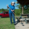 Janet Hunley, with Liberty Utilities, sweeps the pavilion at Wildcat Park on Friday during the United Way Day of Action.<br /> Globe | Roger Nomer