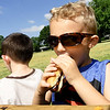 Braylon Smith, 4, enjoys a bite of a hotdog as Emrick Harmon checks out the scenery during the annual Kids Fishing Day on Saturday at Carthage's Kellogg Lake. Free lunch was provided by the Carthage Rotary. The annual event also featured free fishing, educational booths and more.<br /> Globe | Laurie Sisk