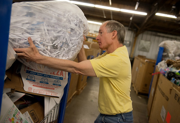 Rick Steere sorts recycling materials on Friday at the Joplin Workshops.<br /> Globe | Roger Nomer