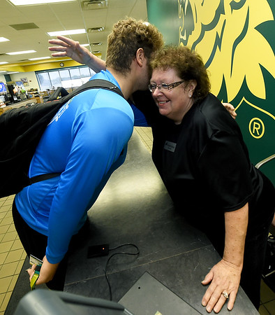 """Missouri Southern football player Aiden Brown, left, gets his daily hug from Denise Terry, affectionately known as """"Momma D"""" to Missouri Southern students as she stands near her cashiers station in the Mayse Dining Hall on Wednesday. terry was recently honored by the MIAA for her service to student athletesT<br /> Gkobe   Laurie Sisk"""