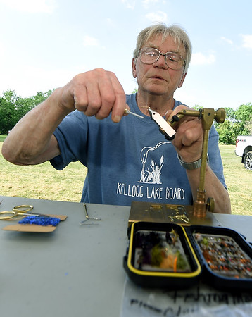 Barrie Towler, of the Kellogg Lake Board, ties off a fly during a demonstration at the annual Kids Fishing Day on Saturday at Carthage's Kellogg Lake. The annual event featured free fishing, educational booths, free lunch and more.<br /> Globe | Laurie Sisk