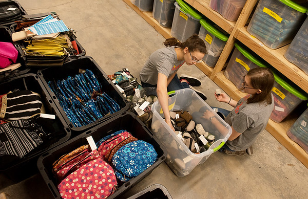 Ellen Anker, 18, and Samantha Owen 14, sort merchandise at Rapha House while volunteering with the Youth Volunteer Corps on Tuesday.<br /> Globe | Roger Nomer