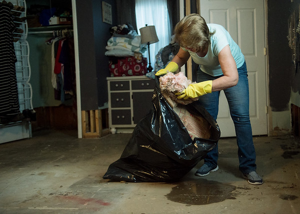 Michelle Embrey removes water-damaged insulation from a friend's house on Riverside Drive in Neosho on Tuesday.<br /> Globe | Roger Nomer