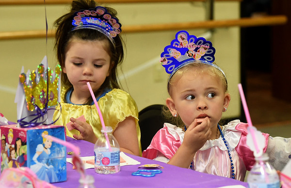"From the left: Kenzly Allen, 4, of Carthage and kyris Moll, 3, of Jasper enjoy a snack as they listen to a reading of ""Cinderella"" on Wednesday night at Ovation Studios in Carthage during its Princess Academy.  Young girls were treated to princess costumes, story time, dancing and more.<br /> Globe 