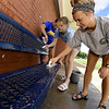 From the left: Miami parks workers Kyah Kingfisher, Amanda Welch and Haley Basker, Miami Pool assistant manager, clean grime off a bench in preparation for opening of the pool , which is targeted for June 22. The pool has yet to open for the season after heavy flooding buried the pool and its grounds.<br /> Globe | Laurie Sisk