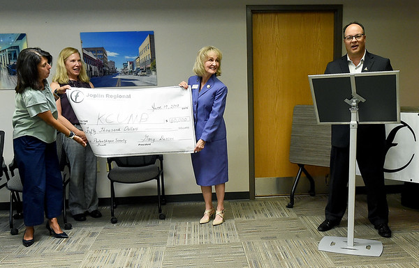 From the left: CASA Treasurer Suzanne Hall, CASA Vice President Lori Smith and Kansas City University Campus Dean Laura Rosch hold one of two checks for $50,000 presented to both CASA and KCU by the Joplin Regional Community Foundation's Philanthropic Society as chairman of the foundation, Bryan Vowels looks on at the Joplin Area Chamber of Commerce on Thursday.<br /> Globe | Laurie SIsk