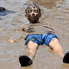 Twelve-year-old Logan Spratley, of Joplin, relaxes in a pool of cool, muddy water during the annual Mudstock event on Saturday in Carthage. The event is sponsored by the Alliance of Southwest Missouri.<br /> Globe | Laurie Sisk