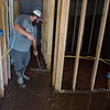 Matt Townsend cleans mud out of his wife's salon in Anderson on Tuesday.<br /> Globe | Roger Nomer