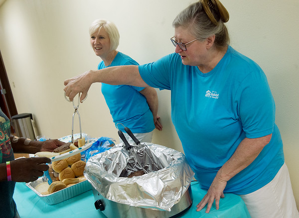 Julie St. Clair, Habitat board member, left, and Gayla McCurdy help serve lunch during a 30th anniversary party at the Habitat ReStore on Thursday.<br /> Globe | Roger Nomer