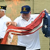 Bob Harrington, of American Legion Post 13 helps retire one of dozens of U.S. flags during a Flag Day flag retirement ceremony on Friday night outside Memorial Hall. Representatives from the City of Joplin, Joplin Police and Fire and local Boy Scouts also assisted with the ceremony.<br /> Globe | Laurie SIsk