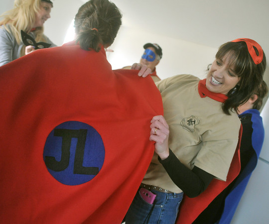 Globe/Roger Nomer<br /> April Foulks puts a cape on fellow Justice League member Ashley Norman before the dedication ceremony for 2630 Wall on March 13, 2013.