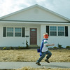 Globe/Roger Nomer<br /> Justice Moore, 4, grandnephew of the Kunces, runs by the completed house at 2630 Wall in a mask and cape made for him by the Justice League on March 13, 2013.