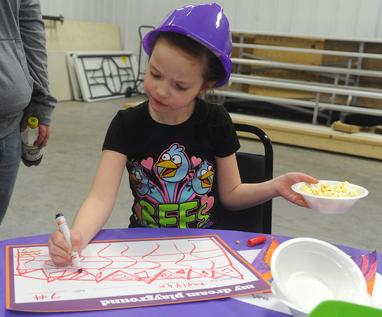 Globe/Roger Nomer<br /> Kaylynn Damrill, 7, demonstrates the important skill of balancing a snack while desiging a playground during a meeting at Community Support Services of Missouri on Tuesday.  Playground company KaBoom!, with funding support from the McDonald's Foundation, will be building a playground at Community Support Services on May 31.  Those interested in volunteering for the build are encouraged to contact Community Support Services.