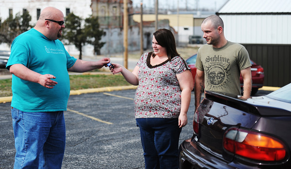 Globe/T. Rob Brown<br /> Brad Campbell, a case manager with Catholic Charities of Southern Missouri, hands the keys to a Chevy Malibu over Friday afternoon, March 15, 2013, to Erik Smith and Lori Curry, of Joplin. The couple lost their car in the tornado.