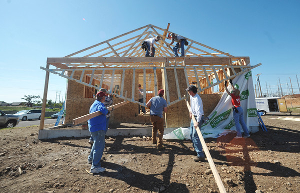 Globe/Roger Nomer<br /> Volunteers help lift tresses to top off the house at 2630 Wall on the third day of construction at the site.