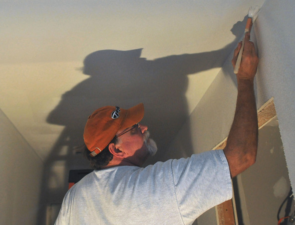 Globe/Roger Nomer<br /> Bill Ideker paints a hallway inside 2630 Wall on Nov. 12, 2012.  Friends and family of the homeowners turned out to help with the exterior portions of the house during several work days.