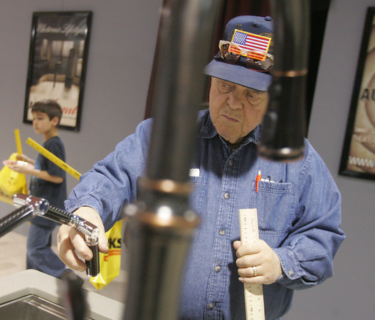 Globe/Roger Nomer<br /> Bill Grimmett, Webb City, checks out a faucet at the Distinctive Home Products booth at Friday's Home Builders Show at the Holiday Inn Convention Center.
