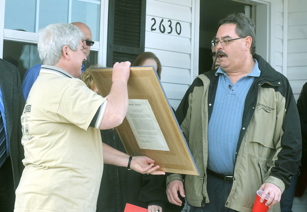 Globe/Roger Nomer<br /> Ed Kunce reacts as Christine Beydlern presents him with a signed print of Brooks Robinson as a house warming present on Wednesday.