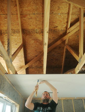 Globe/Roger Nomer<br /> Brent Phillips, owner of Phillips Drywall, hammers ceiling panels into place at 2630 Wall in mid-December.