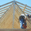 Globe/Roger Nomer<br /> Ryan Scheuermann, Habitat site supervisor, attatches tresses to 2630 Wall during a work day in October.