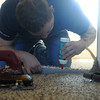 Globe/Roger Nomer<br /> Cody Tubbs, owner of CT's Flooring, works on a carpet seam in 2630 Wall on Tuesday afternoon.