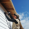 Globe/Roger Nomer<br /> April Foulks, a deputy juvenile officer, nails down siding during a work day in late October at 2630 Wall.
