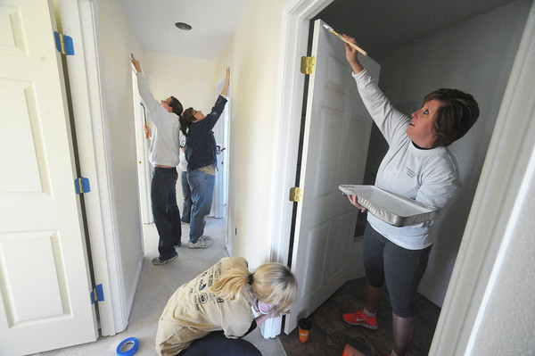 Globe/Roger Nomer<br /> Members of the Justice League, from left, Katrina Richards, Linda Heman, Alison Hershewe and Shelly Dreyer paint trim along doorways at 2630 Wall on February 6, 2013.