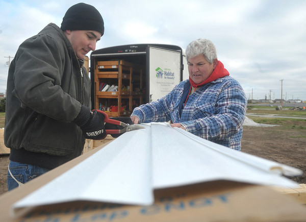 Globe/Roger Nomer <br /> With numb hands on a cold day, Mitchell Mauller, a Jasper County deputy, and Christine Beydler cut siding for 2630 Wall in late October.
