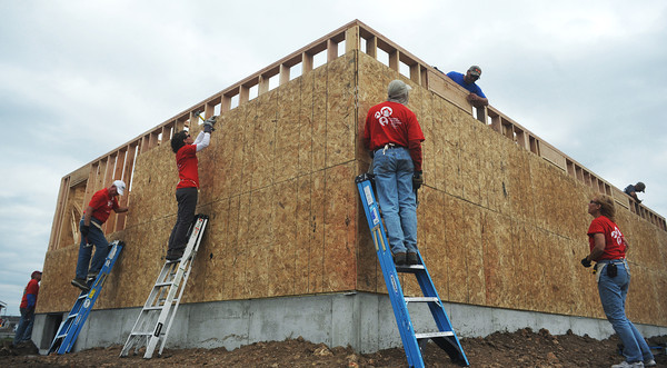 Globe/Roger Nomer<br /> Volunteers with the Thrivent Financial organization help the walls take form at 2630 Wall.  On the second day of construction at the site, most of the exterior walls were nailed up.