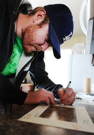Globe/T. Rob Brown<br /> Rebuild Joplin supply and logistics coordinator Benjamin Costley signs a frame for a welcome mat Tuesday afternoon, March 19, 2013, at the new home of Wes and Susie Lamar.