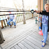 Co-owner of River's Bend Ann Galbreath launches a water balloon across Shoal Creek from the deck of her bar and grill on Tuesday night.<br /> Globe | Laurie Sisk