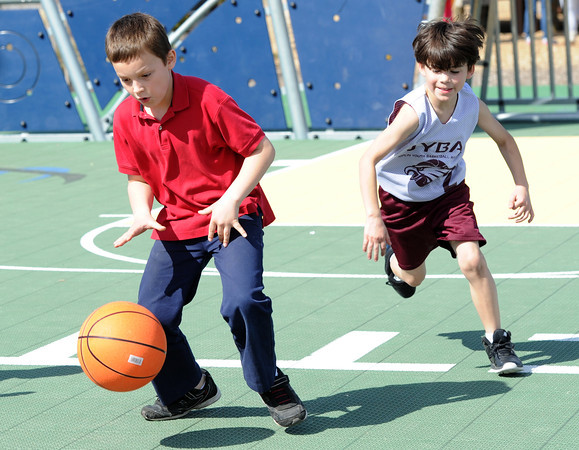 Eight-year-old Jett Beal, right, tries to catch up to nine-year-old Jerimiah Nowak as they play basketball on Friday afternoon at Cunningham Park.<br /> Globe | Laurie Sisk