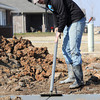 Bud Davis fashions grooves into the sidewalk of an almost completed home at 2142 Florida on Thursday.<br /> Globe | Laurie Sisk