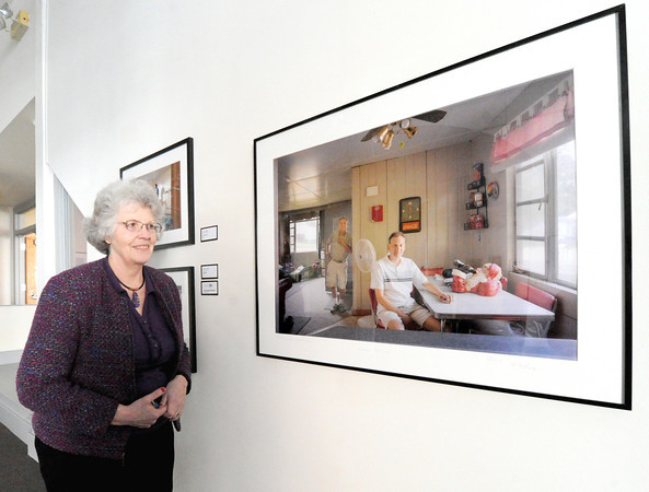 "Spiva Office Manager Linda Kyger talks about the longevity of the Photo Spiva exhibition as she stands near third place winner ""Jeff and Dad - Haunted House"" Cleveland, Ohio photographer Charles Jeffrey Mintz.<br /> Globe 