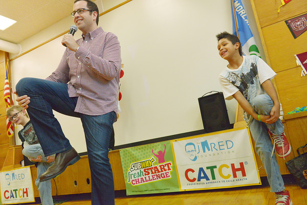 Globe/Roger Nomer<br /> Jared Fogel leads Eastmorland Elementary students including third graders Aiden Edwards, left, and Terrance Gibson in exercises during a visit to the school on Friday. Fogel, who became famous by losing weight on a Subway diet, was at the school to talk about childhood obesity and introduce the Subway Fresh Start Challenge.