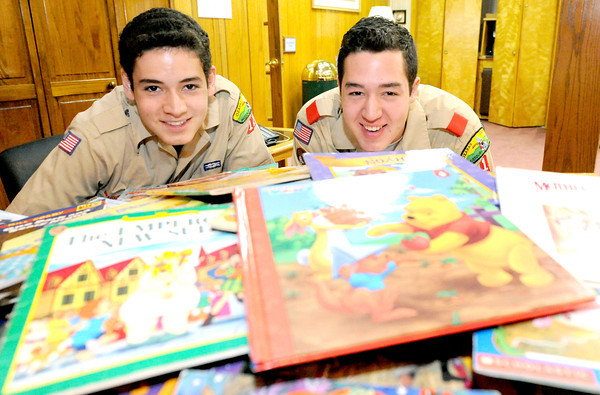 Fifteen-year-old brothers Nathan Salyer, left and 17-year-old Zach Salyer sit near the hundreds of books they have collected and plan to donate to NALA.<br /> Globe | Laurie Sisk