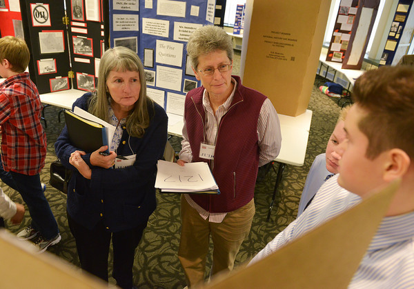 Globe/Roger Nomer<br /> Judges Billie Skelley, left, and Lorinda Hackett listen to a presentation by Landon Moore and Jack Adams, right, both sixth graders at Joplin East Middle School at History Day at Missouri Southern on Friday.