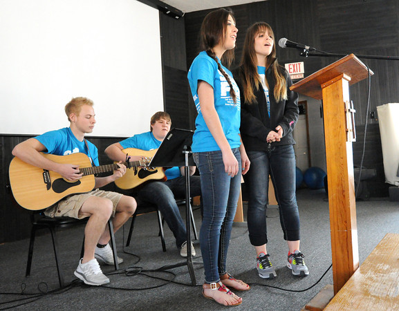 College Heights Christian School students sing Christian music for children at Life House's after school program on Tuesday as part of their Missions Week. From the left: Nathan Adrian, Coltin Woodward, Courtney Byrne and Katie Barnett.<br /> Globe | Laurie Sisk