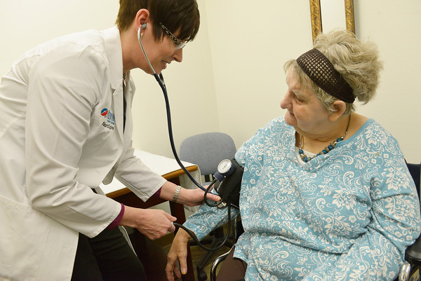 Globe/Roger Nomer<br /> Jennifer Theis takes a blood pressure reading from Betty Lawrence at the Freeman Neurospine Center on Tuesday morning.