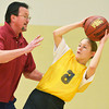 Globe/Roger Nomer<br /> Coach Keith Patterson helps LaShayla Gillespie, 18, with a passing offense during practice for the Special Olympics basketball team on Tuesday at Neosho Junior High School.